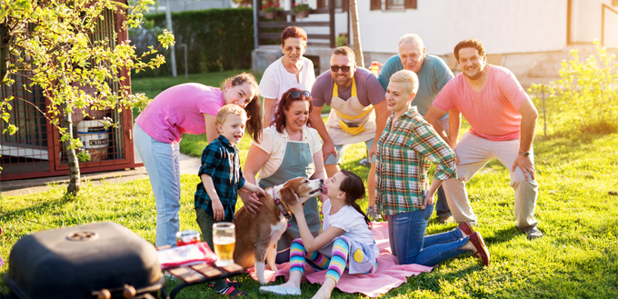 family barbecuing with their dog