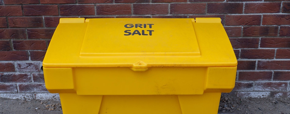 Yellow Grit Salt Bin against Brick Wall