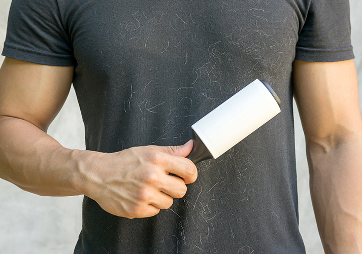 Man holding a hair removal roller.