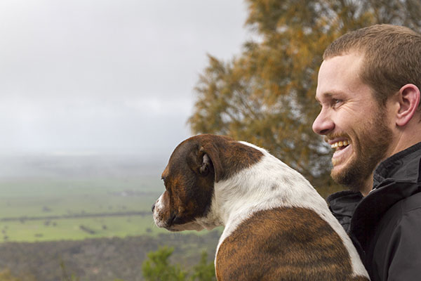 Solitary man aged 30, with his dog, outdoors with a stormy sky in the background
