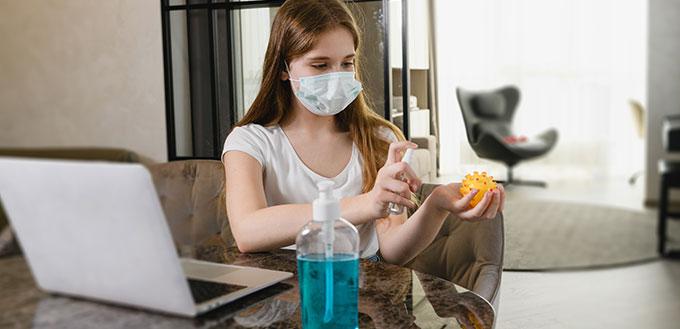 Les jeunes femmes restent à la maison pendant la quarantaine épidémique mondiale, portent un masque de protection, utilisent un antiseptique pour ordinateur portable, jouet pour chien et mains